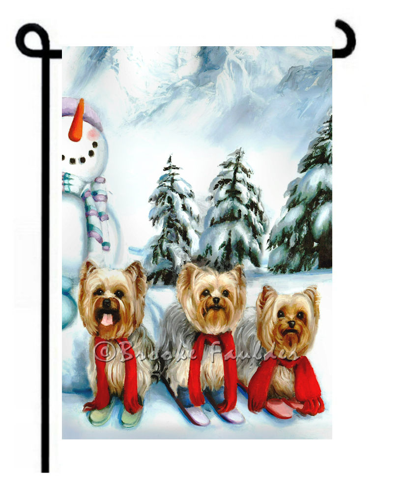 3 yorkies downhill skiing amongst snowman and pine trees