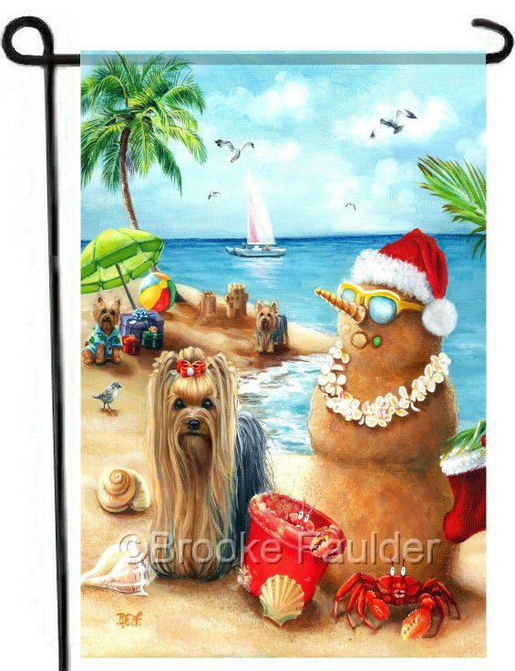Christmas garden flag with yorkies and sandman and red crabs on a beach of fine sand on the ocean. The sandman wears a Santa hat and hawaiian lei.