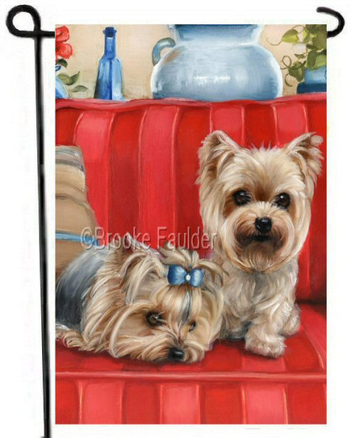 Two yorkies on a red striped sofa. This garden flag is 12 x 18 inches. One dog rests with her head down while the other sits beside her.