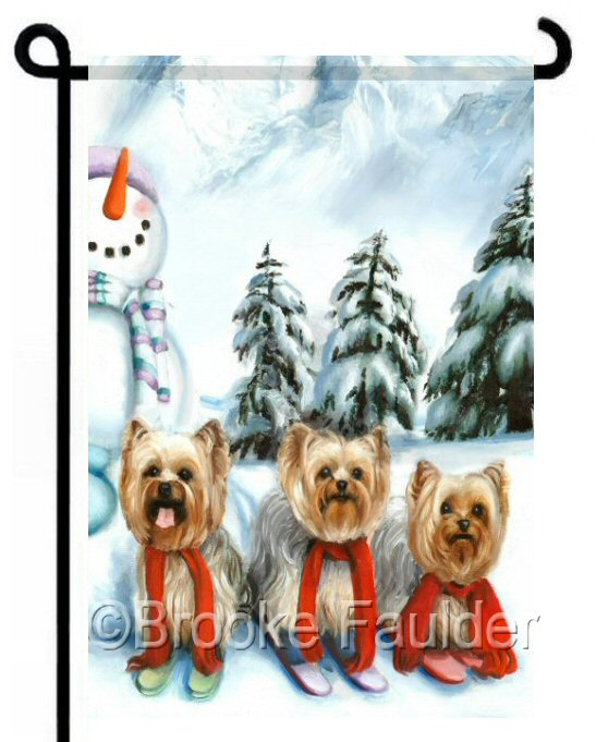 3 Yorkies ski down a mountain and pass a snowman dressed up in a scarve, gloves and hat. Pine trees and mountains in the background. Colors of mostly light blue help the dogs stand out on this cute small dog garden flag.