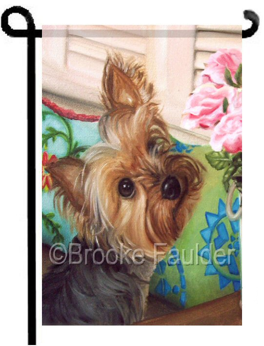 A Yorkie with a puppy-cut stares a grouping of pink roses, decorative throw pillows decorate a window seat and the shutters are closed in this colorful dog garden flag.