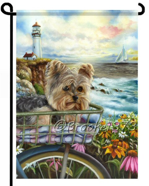 12 x 18 inch garden flag with yorkie in bicycle basket on a morning ride in front of the ocean. wildlfowers are in bloom, a lighthouse beacons the ships at sea and waves crash in against the rocks below.