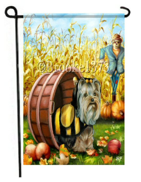 Country Yorkie dressed in bee halloween costume. a scarecrow stands watch over the cornfield and pumpkins and apples are scattered in the yard on this bright colorful dog art flag.