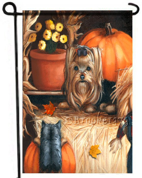 Hay Day garden flag featuring an adult Yorkshire Terrier and a Yorkie puppy in an Autumn scene with pumpkins, a pot of yellow chrysanthemums (mums), corn stalks, a bail of hay and autumn leaves.