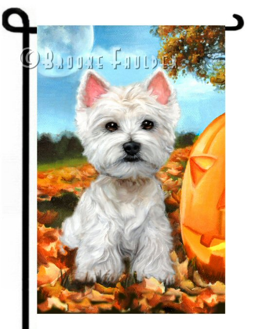 Westie puppy for flowerbed display in autumn beside carved pumpkin and fallen leaves
