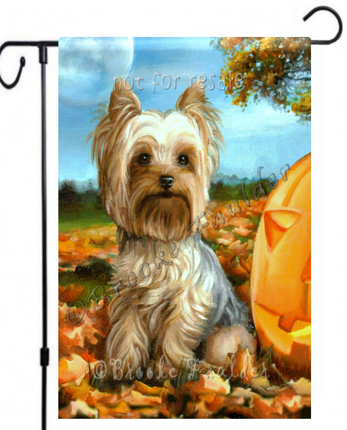 Autumn Yorkie outdoor decor with fallen leaves, pumpkin and full moon in twilight sky.
