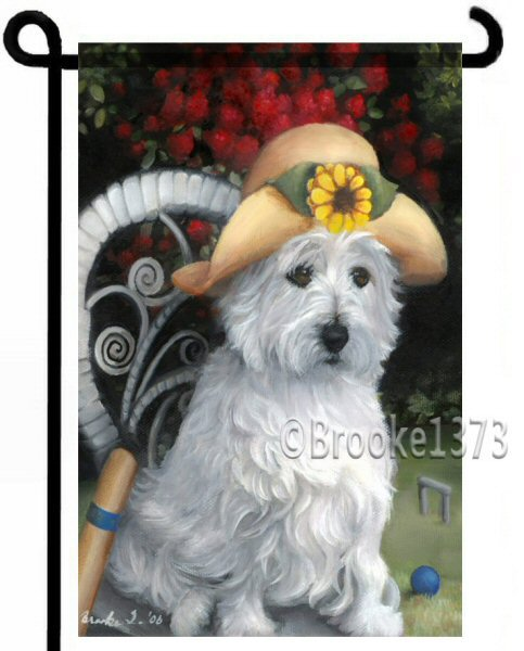 West Highland White Terrier garden flag. The Westie wears a straw hat with a sunflower as a game of croquet seems imminent. The dog sits on a wicker chair and a flowering shrub in a show of red blooms adds color to the flag and your garden!